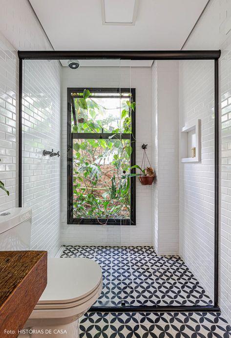 Banheiro com azulejo branco por todo banheiro, piso de ladrilhos hidráulicos em tons de preto, box de vidro e vaso sanitário branco.