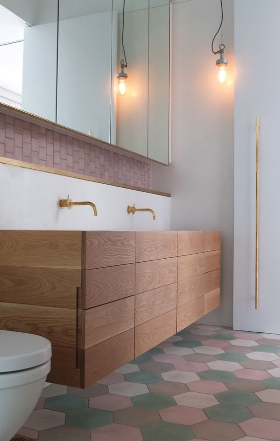 Banheiro com ladrilhos coloridos, gabinete de madeira com detalhes dourado e revestimento rose na parede