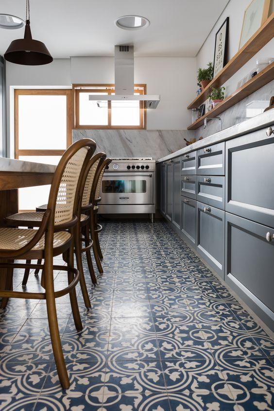 Cozinha com ladrilho hidráulico azul com estampa floral, armário azul, prateleiras de madeira, cadeira de palha e fogão industrial com coifa.