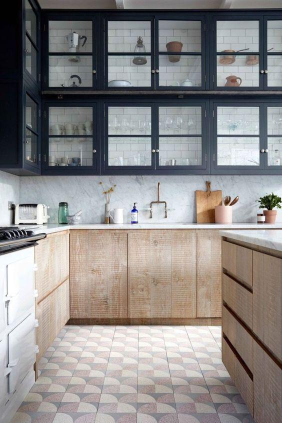 Cozinha com armários preto e amadeirado, ladrilhos no piso e porcelanato em meia parede.