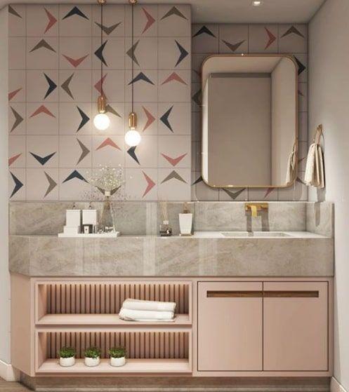 Banheiro com azulejo de ladrilhos hidráulicos moderno, gabinete rosa, pia de mármore cinza, luminária pendente dourada e detalhes do banheiro.