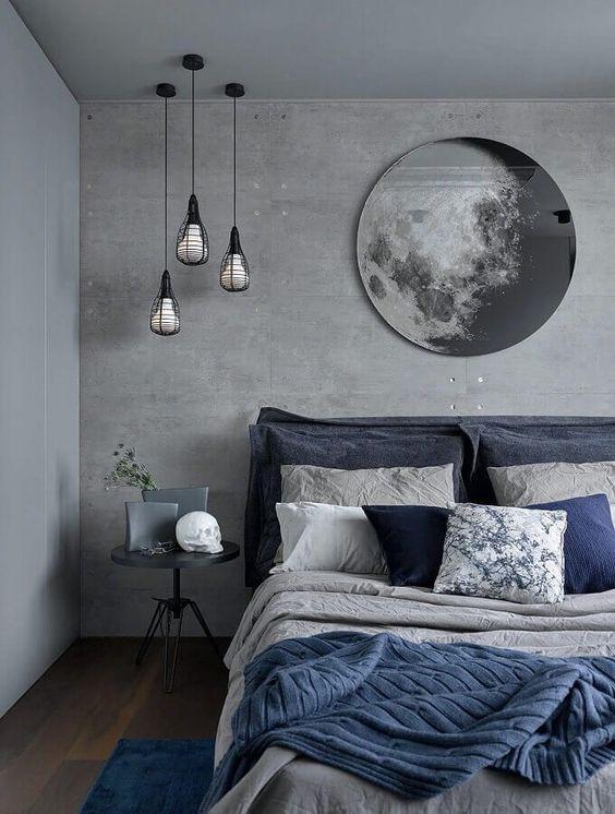 Quarto com parede de cimento queimado, cama de casal com jogo de cama azul e cinza, piso de madeira, tapete azul, mesinha de canto cinza e luminária pendente.