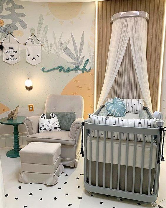 quarto de bebe pequeno unissex com tons verde e laranja, com papel de parede personalizado, berço cinza com mosqueteiro de teto, poltrona cinza com almofadas.