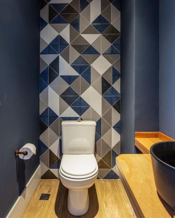 Banheiro pintado de azul, azulejo degrade branco e cinza, detalhes e piso em madeira
