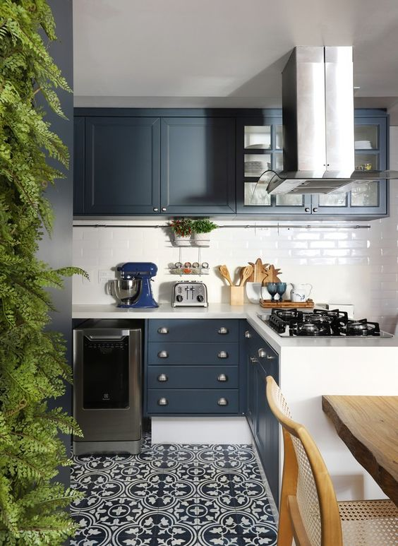 Cozinha moderna com armário azul com detalhes brancos, piso de ladrilho hidráulico e mesa de madeira.