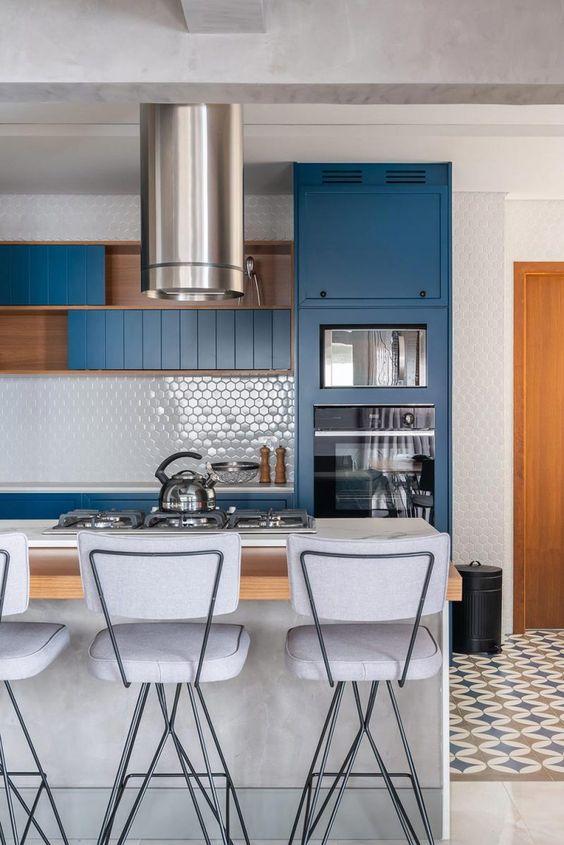 Cozinha moderna com armário azul e detalhes marrom, bancada com revestimento de madeira e bancos brancos, piso com ladrilhos.