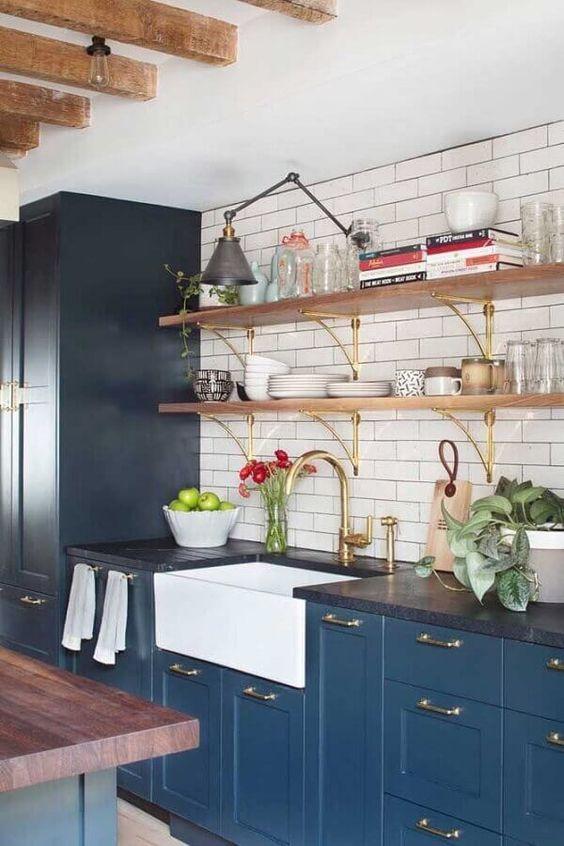 Cozinha moderna com armário azul, detalhes da cozinha na cor dourada, vasos de plantas, prateleiras e bancada de madeira.