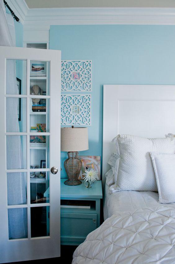 Quarto com parede pintada de azul bebê, cama, porta e detalhes brancos, travesseiros brancos e criado mudo azul bebê.
