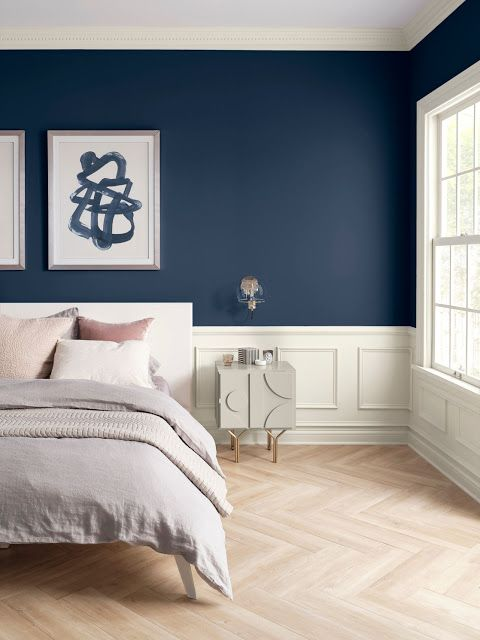 Quarto com parede azul, almofadas, quadro e piso de madeira