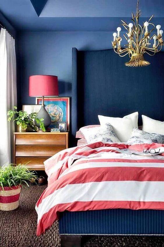 Quarto com vasos de plantas, lustre dourado, parede pintada de azul e acessórios rosa.