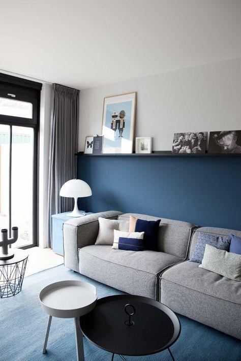 Sala de estar com tapete e parede azul, prateleiras com quadros decorativos, sofá cinza com almofadas em tons de azul, mesa de centro branca e preta