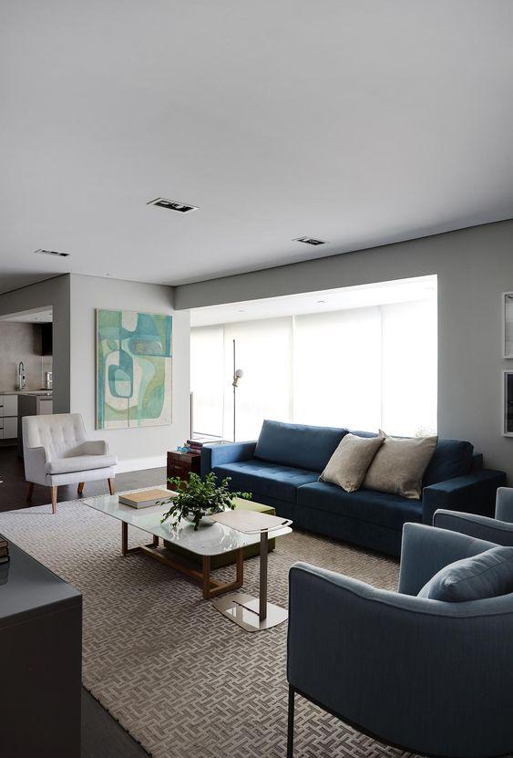 Sala de estar moderna com tapete clean, sofá azul, mesa de centro com vaso de planta, poltrona branca e quadro decorativo na parede.