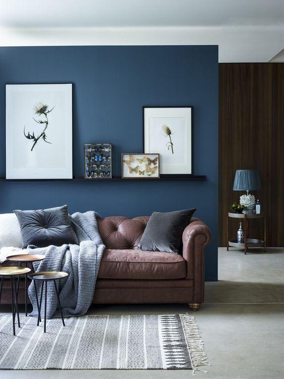 Sala moderna decorada com sofá de couro marrom, piso de cimento queimado, parede azul, almofadas e prateleiras com quadro decorativos.
