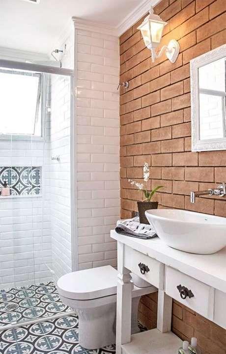 Banheiro com parede de tijolinhos, box de vidro com azulejo do metrô branco, piso com ladrilhos azuis, gabinete branco e louças brancas.