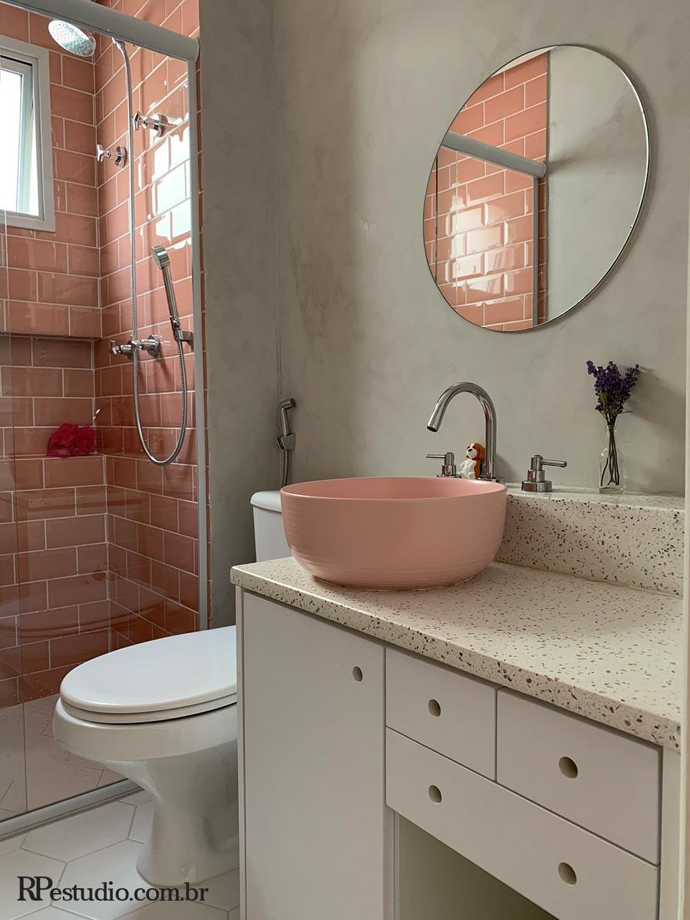 Banheiro com revestimento na parede em cimento queimado, com azulejos e louça na cor rosé