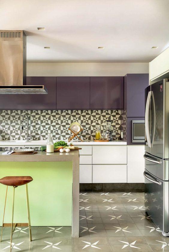 Cozinha com móveis em tons de roxo, bancada de mármore com coluna verde, azulejo de ladrilhos preto e branco e piso de ladrilhos, coifa e geladeira de inox.