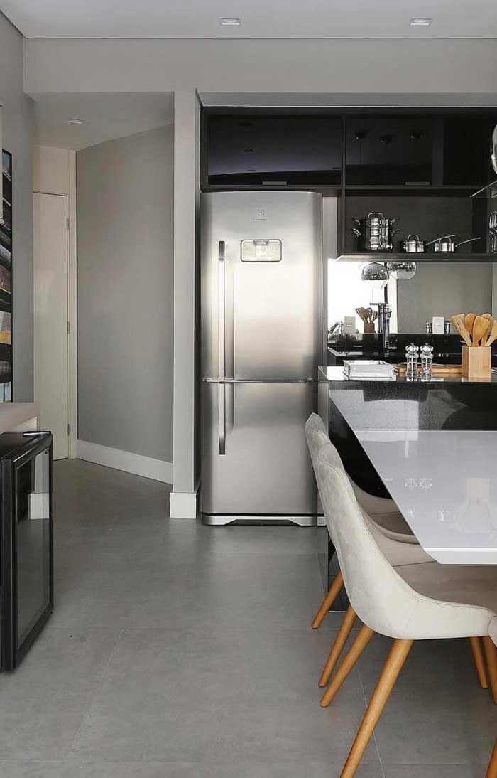 Cozinha em estilo moderno com chão revestido de cimento queimado, tons mais escuros na decoração