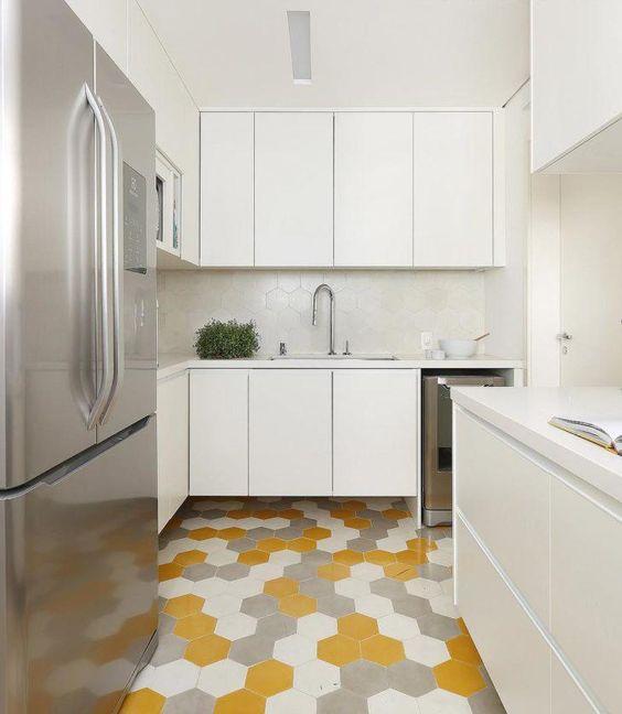 Cozinha com armários brancos, azulejos de ladrilhos brancos, piso de ladrilhos amarelo, cinza e branco e geladeira de inox.