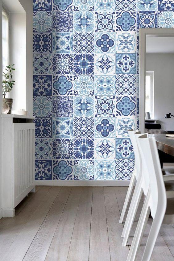 Ambiente com parede revestida de ladrilho hidráulica em tons de azul, piso de madeira, cadeiras brancas e mesa de madeira.