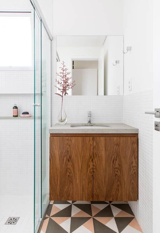 Banheiro com azulejo branco, armário de madeira e piso de ladrilhos cinza, branco e rosa.