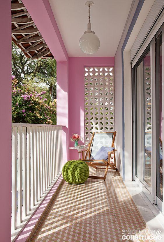 Sacada de casa com paredes pintadas de rosa, cobogó, cadeira de balanço, puff verde e piso com ladrilhos.