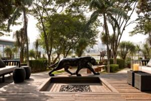 Área externa arborizada com escultura de onça, bancos e puffs e deck de madeira.
