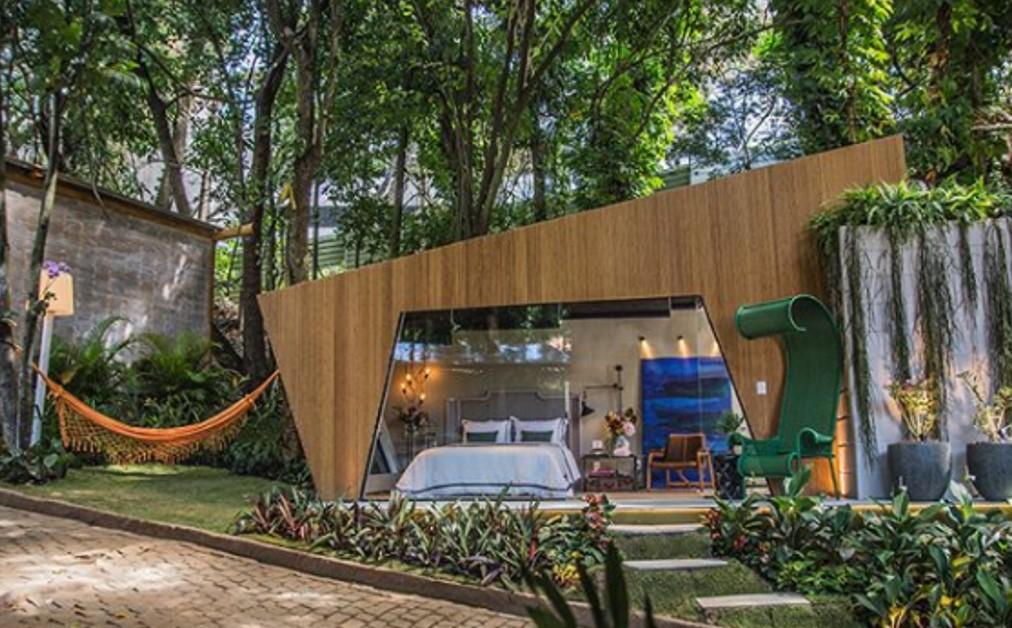 Ambiente Bangalô Suíte de Hóspedes Sumaúma com cama de casal, cadeiras e rede do lado de fora.