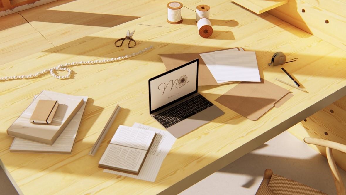 Mesa de madeira com notbook, livros, blocos de anotações, papel e caneta.