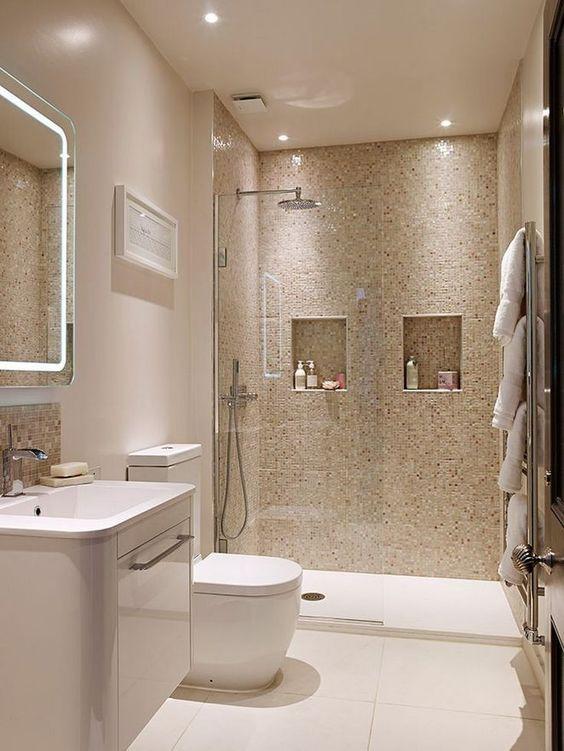 Banheiro com box de vidro e pastilhas na parede, gabinete branco e vaso sanitário branco.