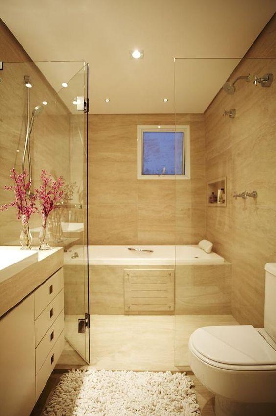 Banheiro com banheira, box de vidro, vaso sanitário branco e tapete.