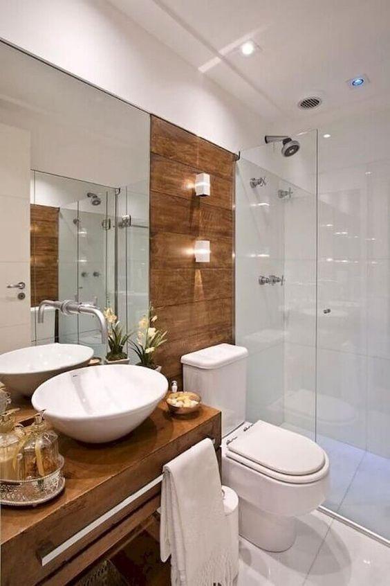 Banheiro com box de vidro, vaso sanitário branco,  cuba branca e gabinete de madeira.