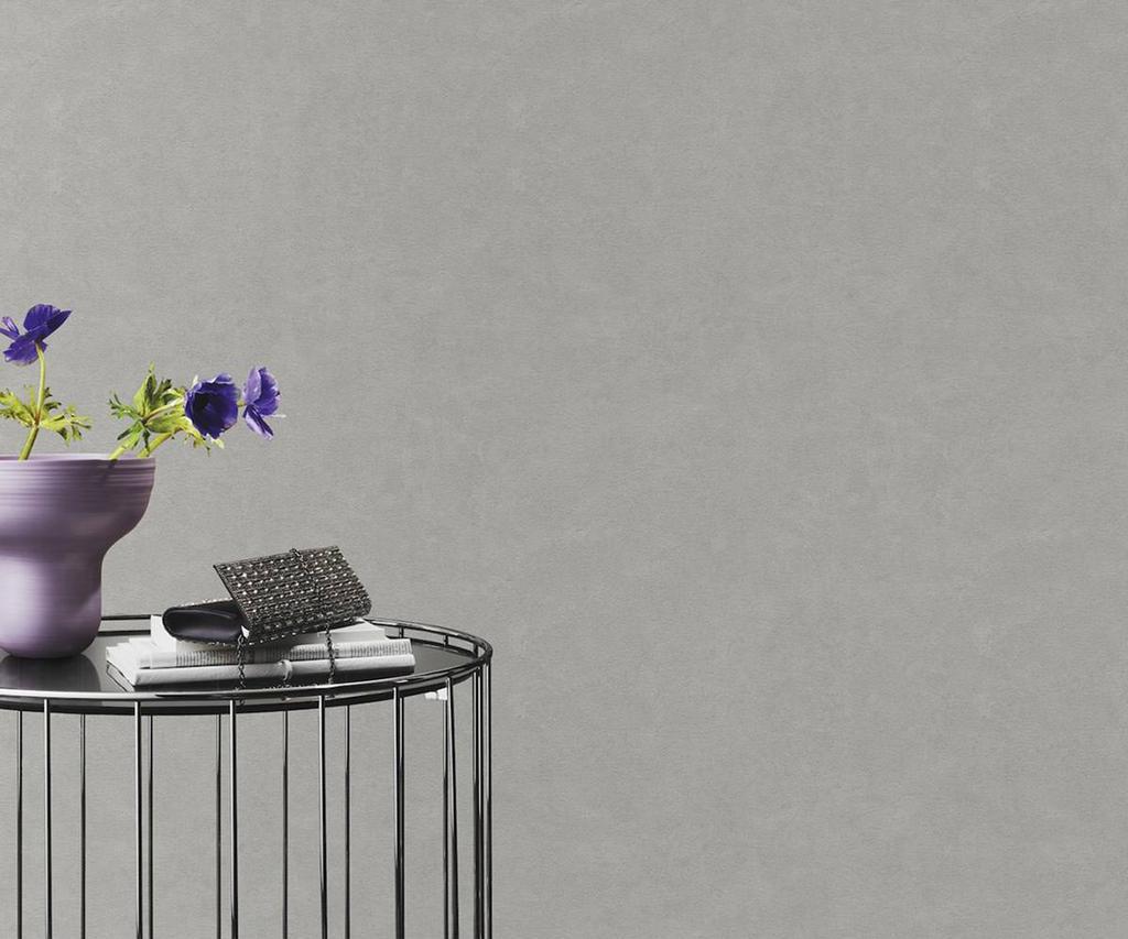 Papel de parede representando cimento queimado e mesa de canto  com vaso e acessórios.