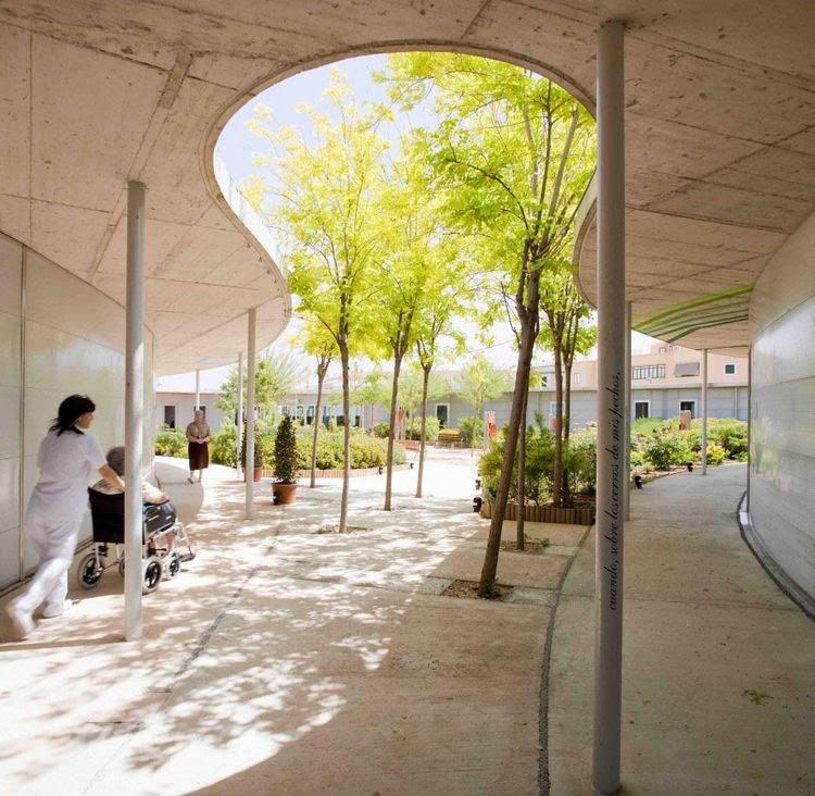 Ambiente externo de hospital com árvores e plantas.