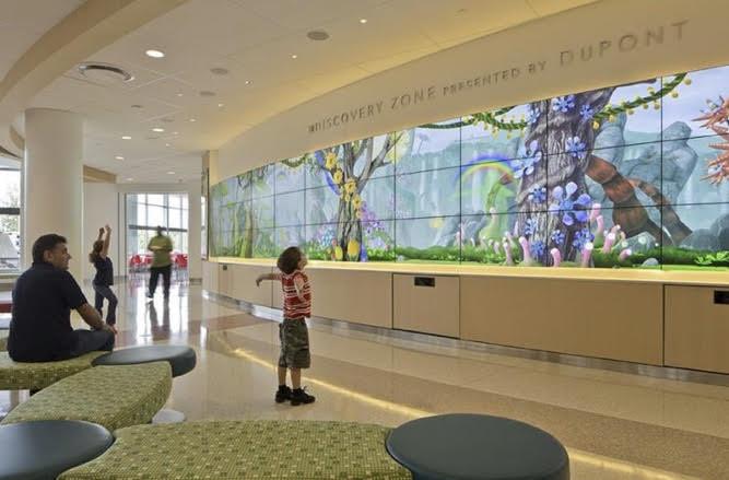recepção de hospital com projeção de LED com imagens infantis.