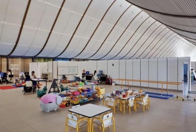 Ambiente de tratamento infantil de hospital com mesas, cadeiras e brinquedos.