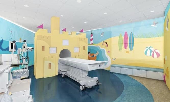Sala de tratamento de hospital com máquina de tomagrafia, paredes coloridas representando praia.
