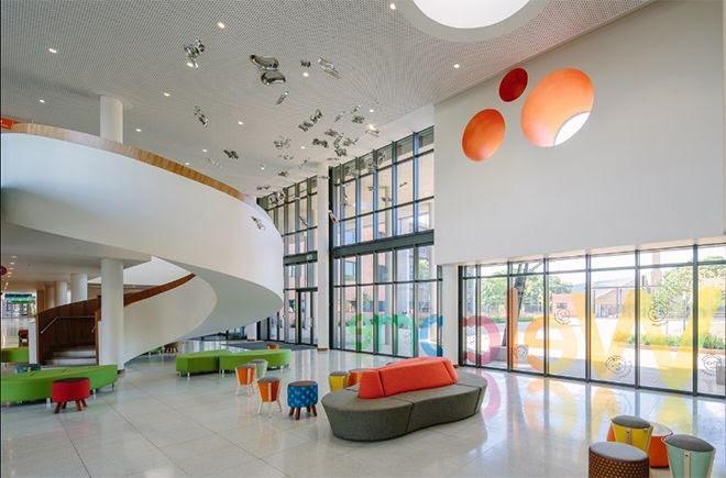 Ambiente de hospital com puffs e sofás coloridos, com escada em caracol larga branca portas de vidro.