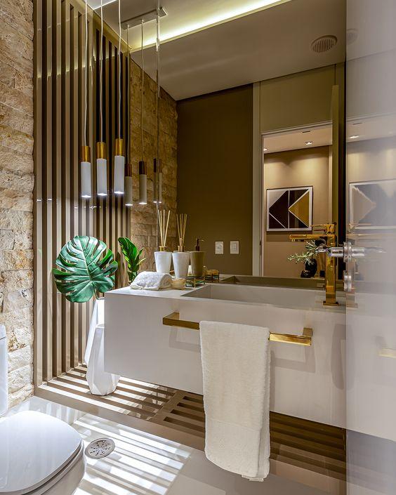 Lavabo com pia branca e acessórios dourados, espelho, planta e vaso sanitário branco.