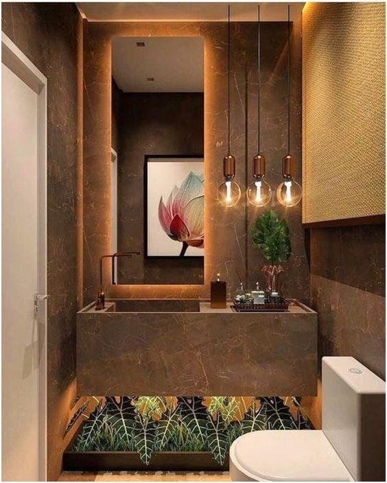 Lavabo em tonas marrons, com planta artificiais, luminárias de teto, pia de porcelanato e vaso sanitários branco.