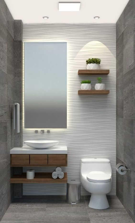 Lavabo com revestimento 3D na parede, espelho retangular, prateleiras de madeira com vasos de planta, pia e vaso sanitário.
