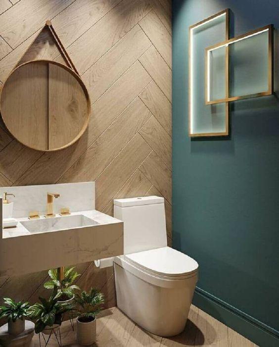 Lavabo com parede verde e parede com revestimento amadeirado, espelho redondo, quadros decorativos e pia de porcelanato branca.
