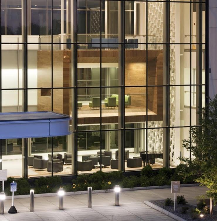 Vista de uma area externa de hospital com arquitetura moderna com fachada de vidro.
