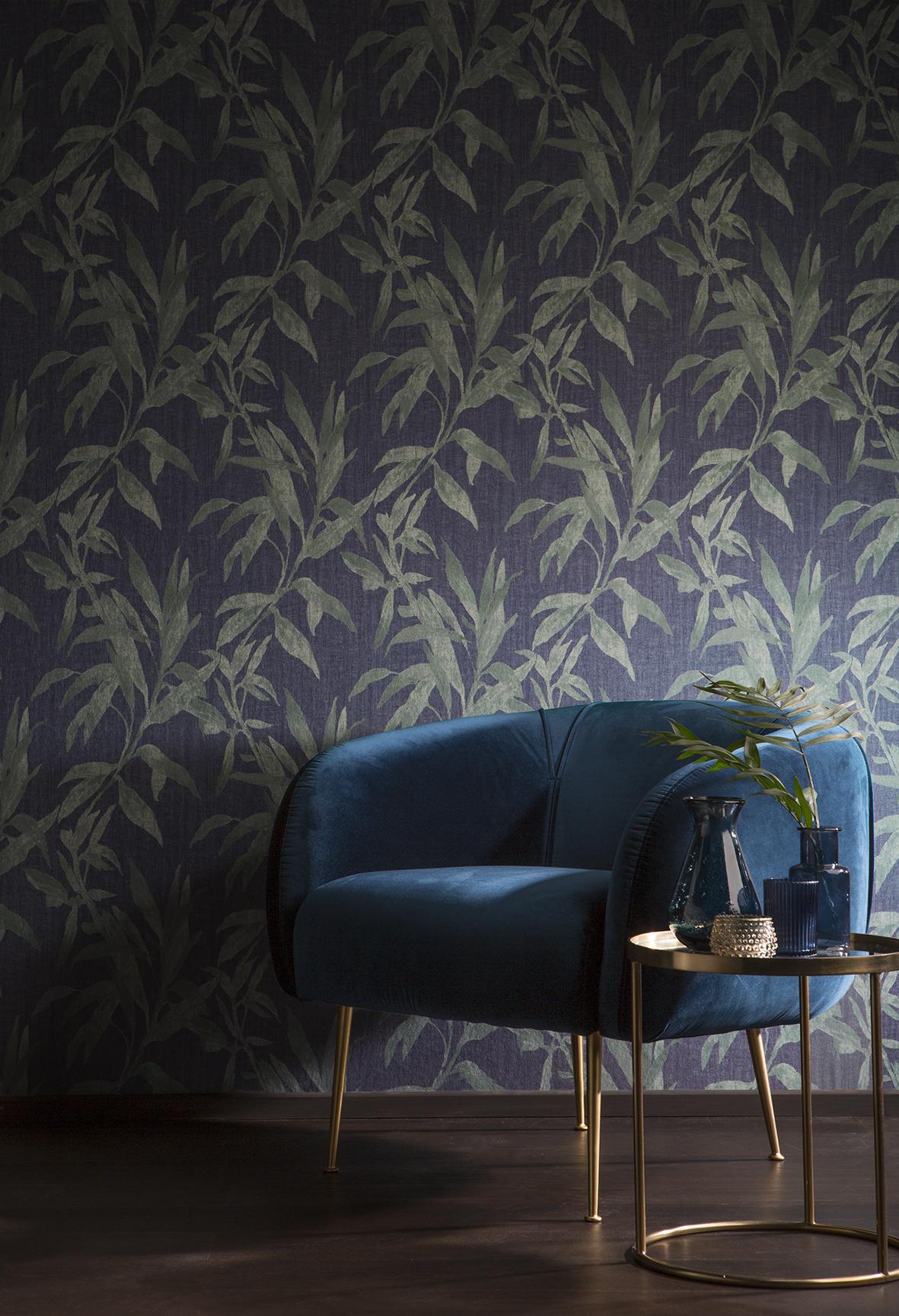 Ambiente com poltrona, mesa de canto e papel de parede azul com plantas verdes.