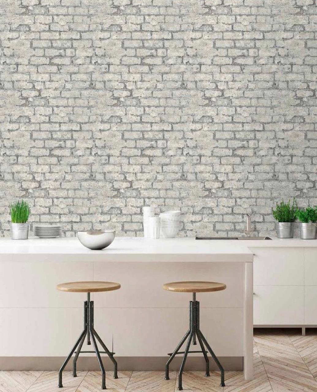 Cozinha com bancada branca, bancos e acessórios de cozinha e papel de parede representando tijolinhos.