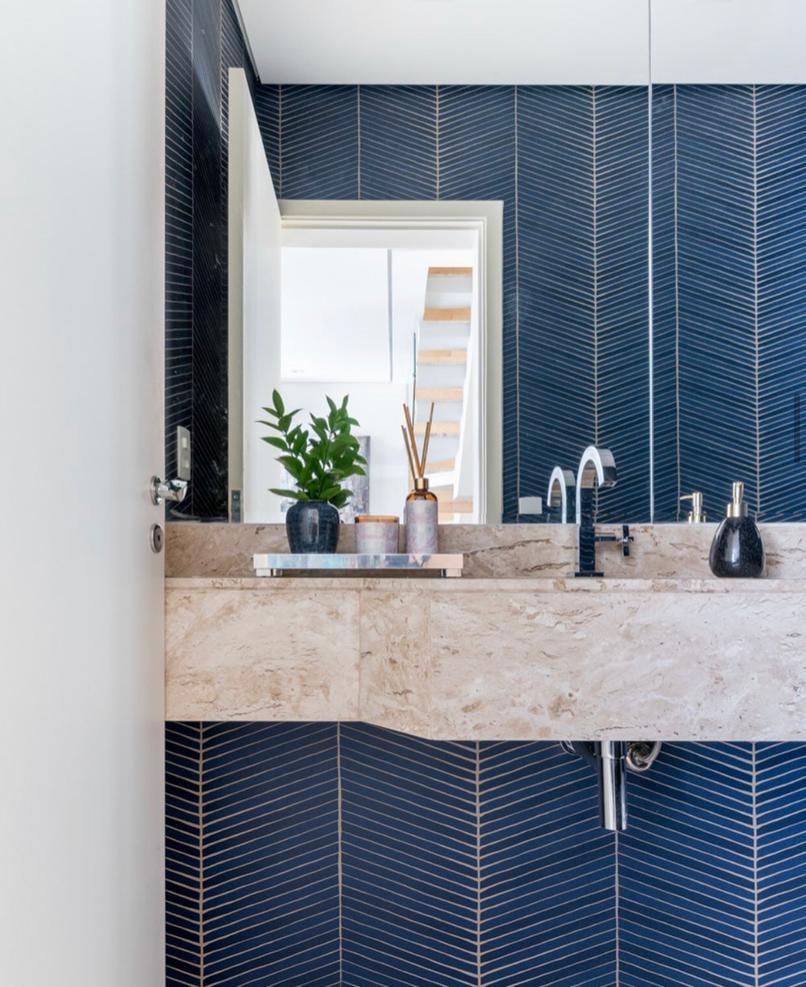 Lavabo com papel de parede azul e pia de mármores com acessórios.