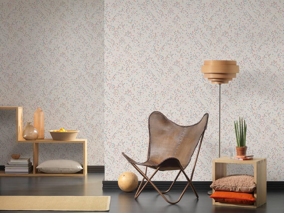 ambiente com papel de parede representando granilite, cadeira, criado mudo com enfeites e almofadas, abajur e nichos.