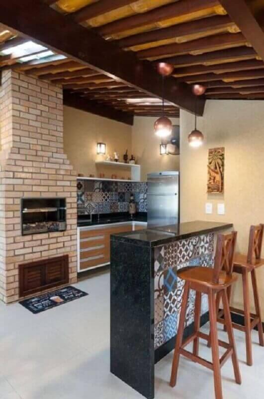 Área externa com churrasqueira feita de tijolinhos. Em estilo rústico possui cadeiras de madeira, bancada, pia de granito preta, piso porcelanato branco e  lâmpadas pendente.