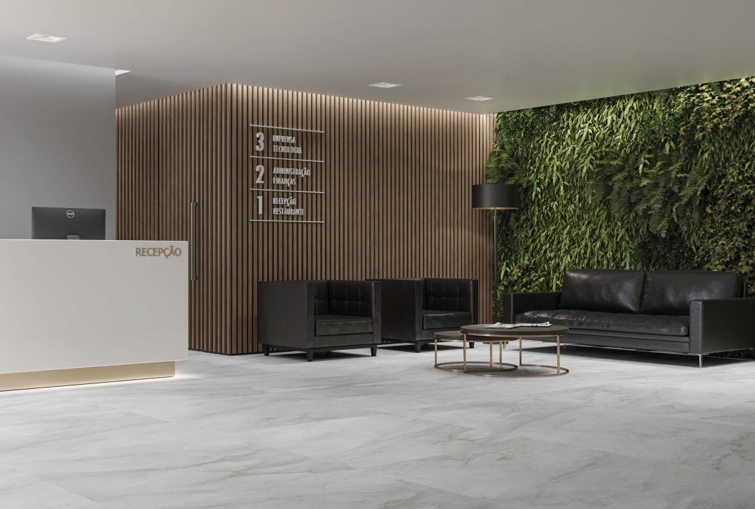 Sala de recepção com sofás de couro e poltronas pretas, jardim vertical, parede divisória com madeira ripada, piso porcelanato superfomato imitando mármore e granito.