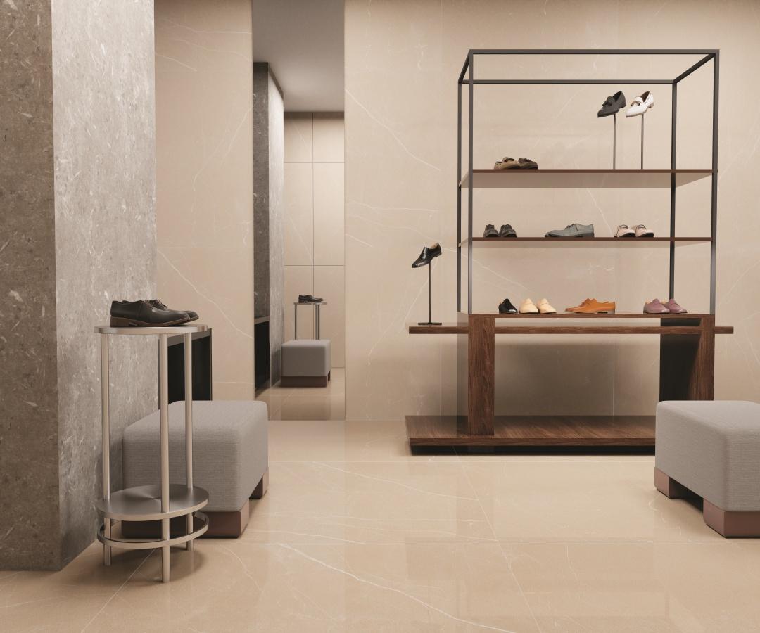 Ambiente com estante de ferro com sapatos, puff cinza, porcelanato superformato cor neutra revestindo piso e parede.