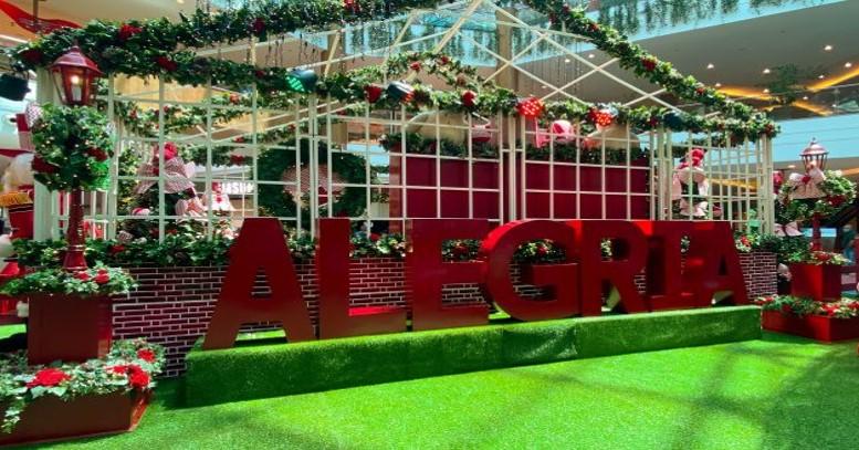 Decoração natalina no pátio principal do shopping com letreiro vermelho escrito alegria